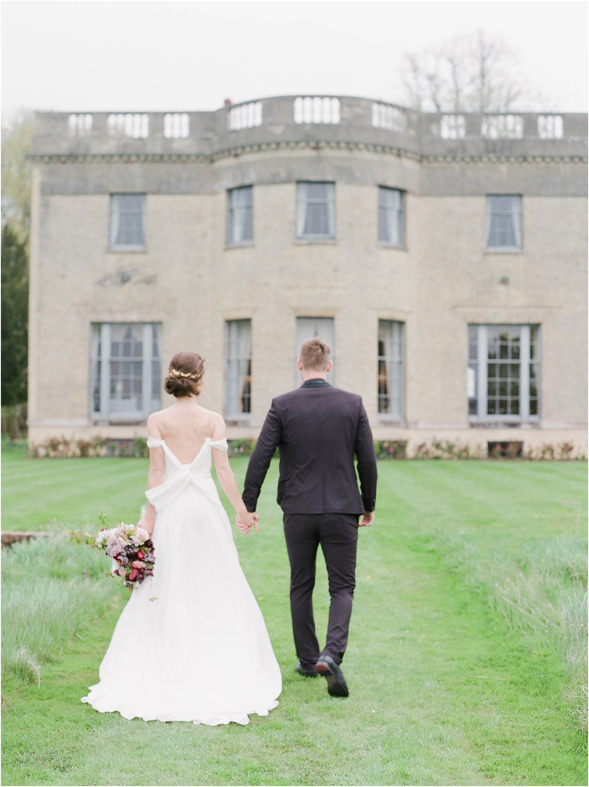 Bride and groom walking towards manor house wedding