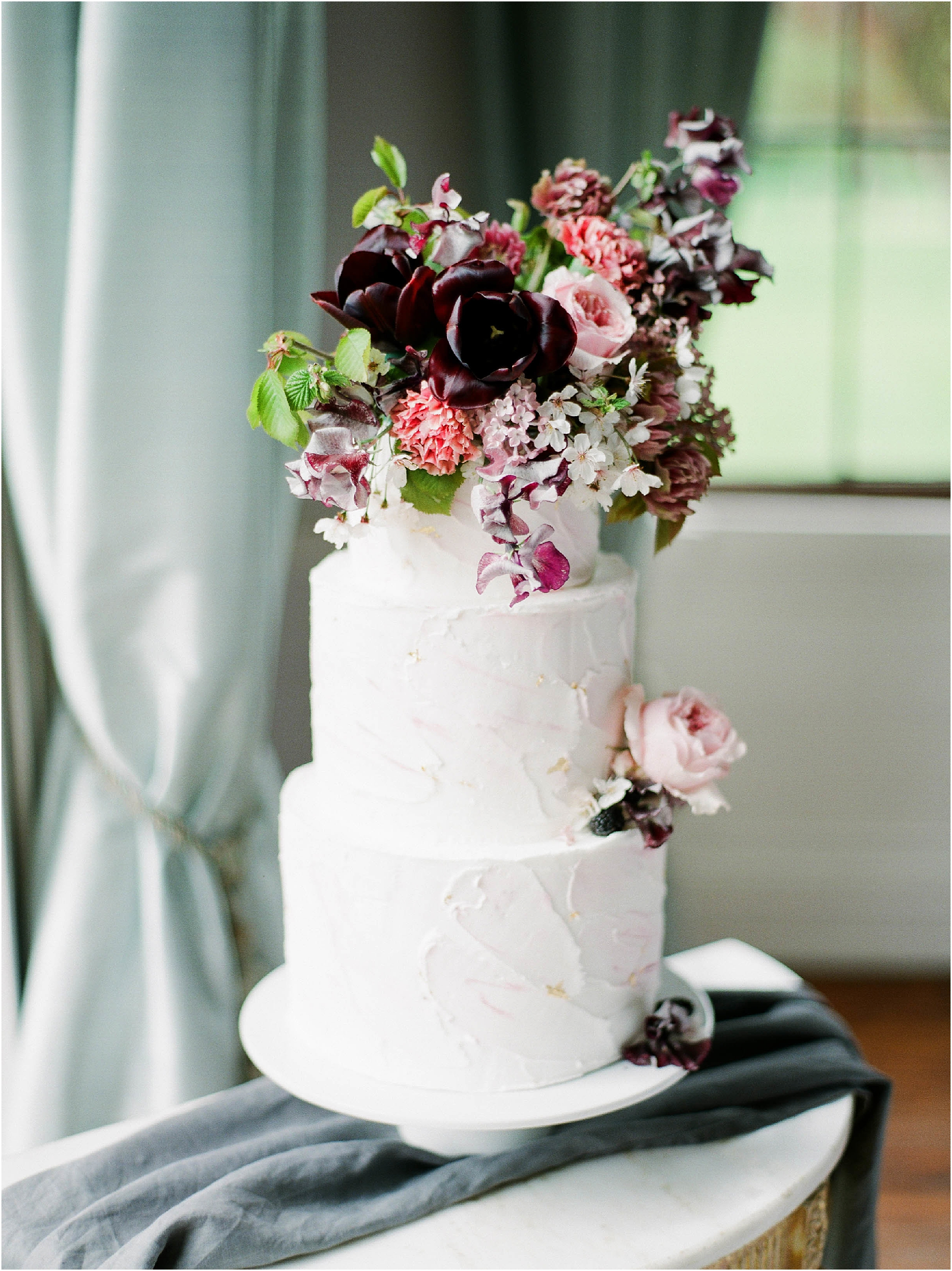 Three tier wedding cake with maroon and pink flowers on it and gold leaf