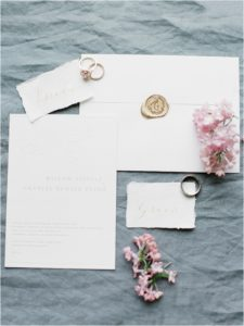 Wedding stationery and rings on grey linen