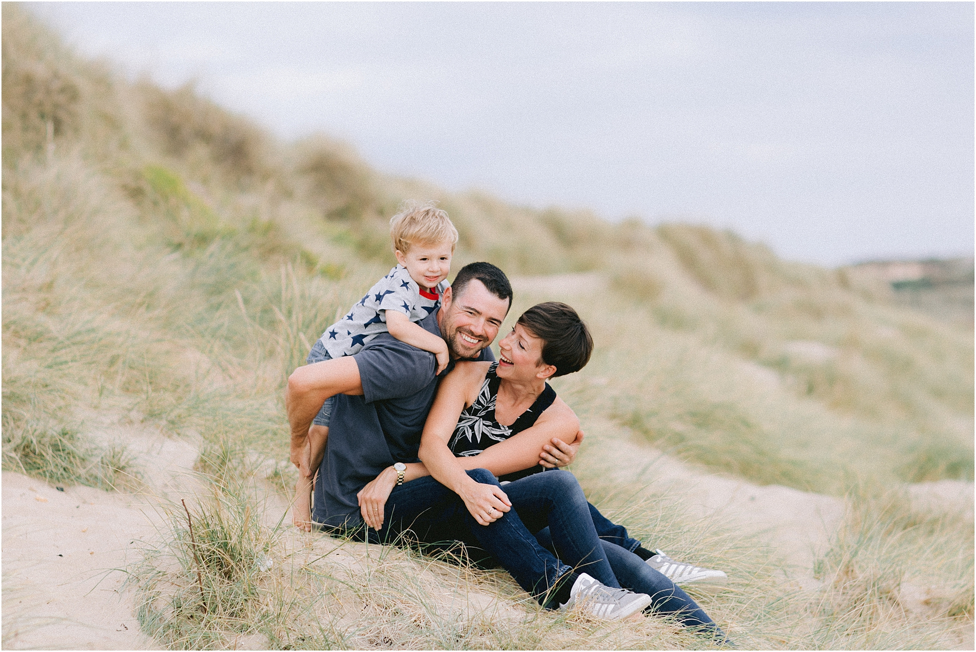 Family of three sitting on sand dune laughing