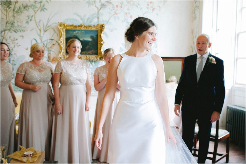 Bride with father of bride and bridesmaids revealing wedding dress