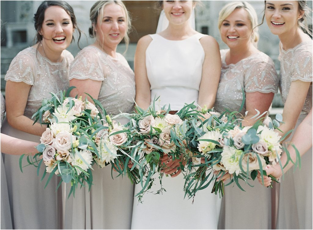 Bride and bridesmaids holding bouquets of roses and eucalyptus