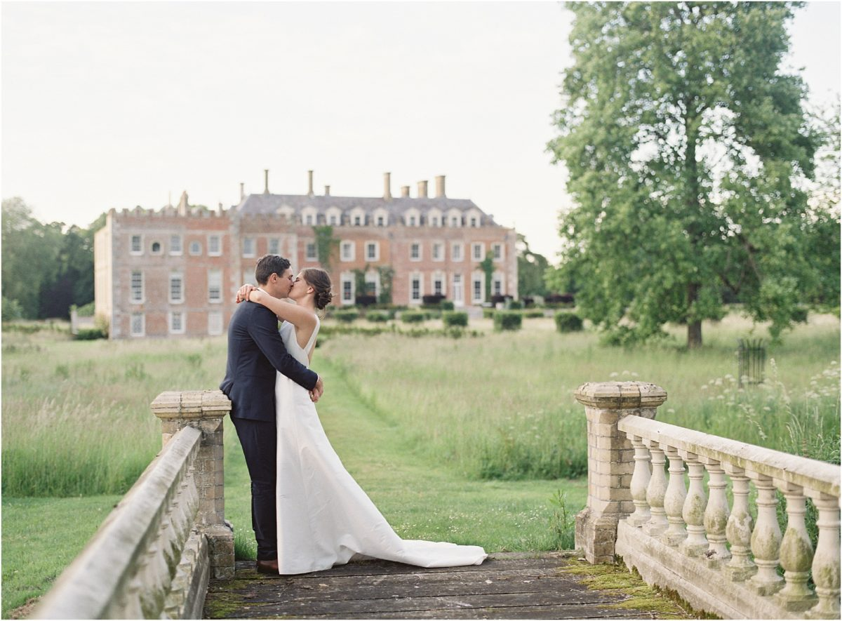Bride and groom kissing on bride at St Giles House wedding