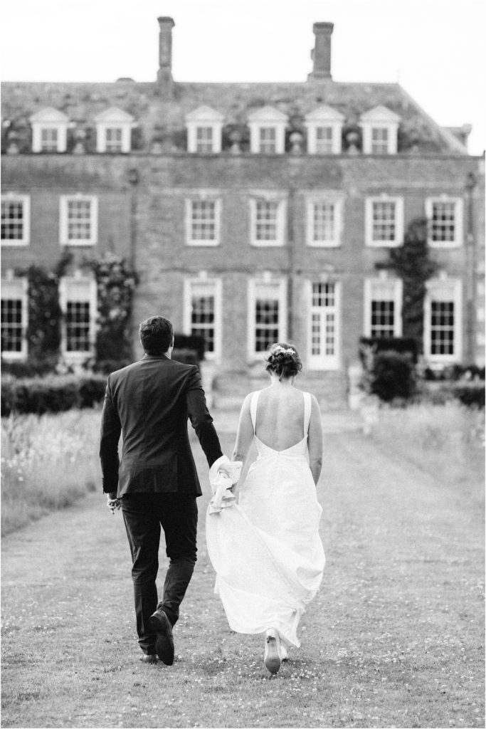 Bride and groom walking away at St Giles House wedding