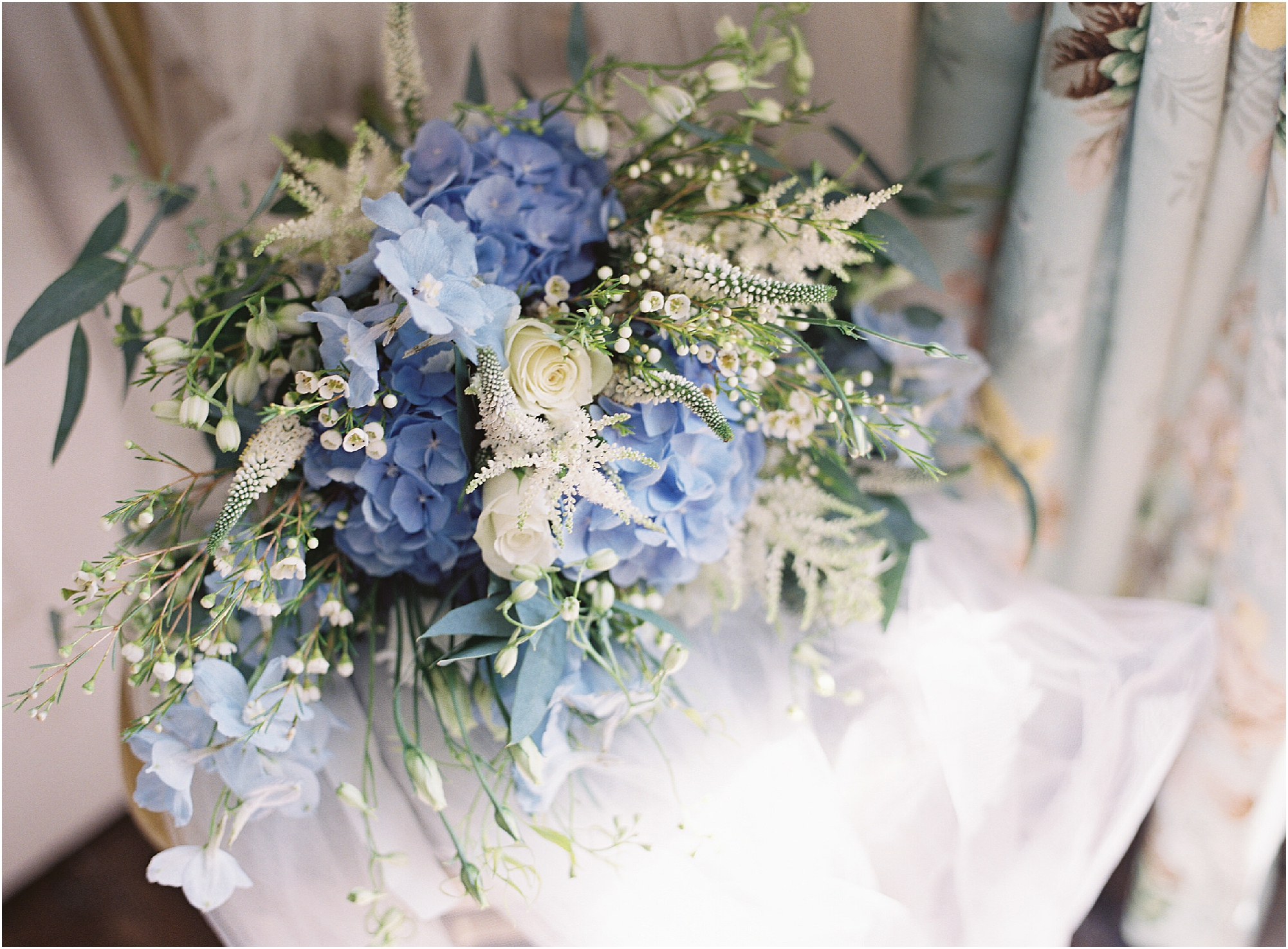 Blue and white bridal bouquet laying on a chair with wedding veil
