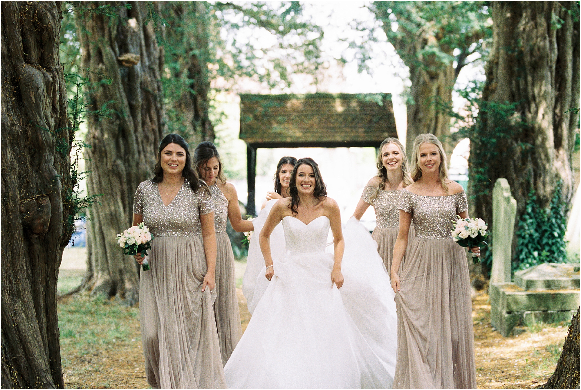 Bride and bridesmaids walking up path to church wedding