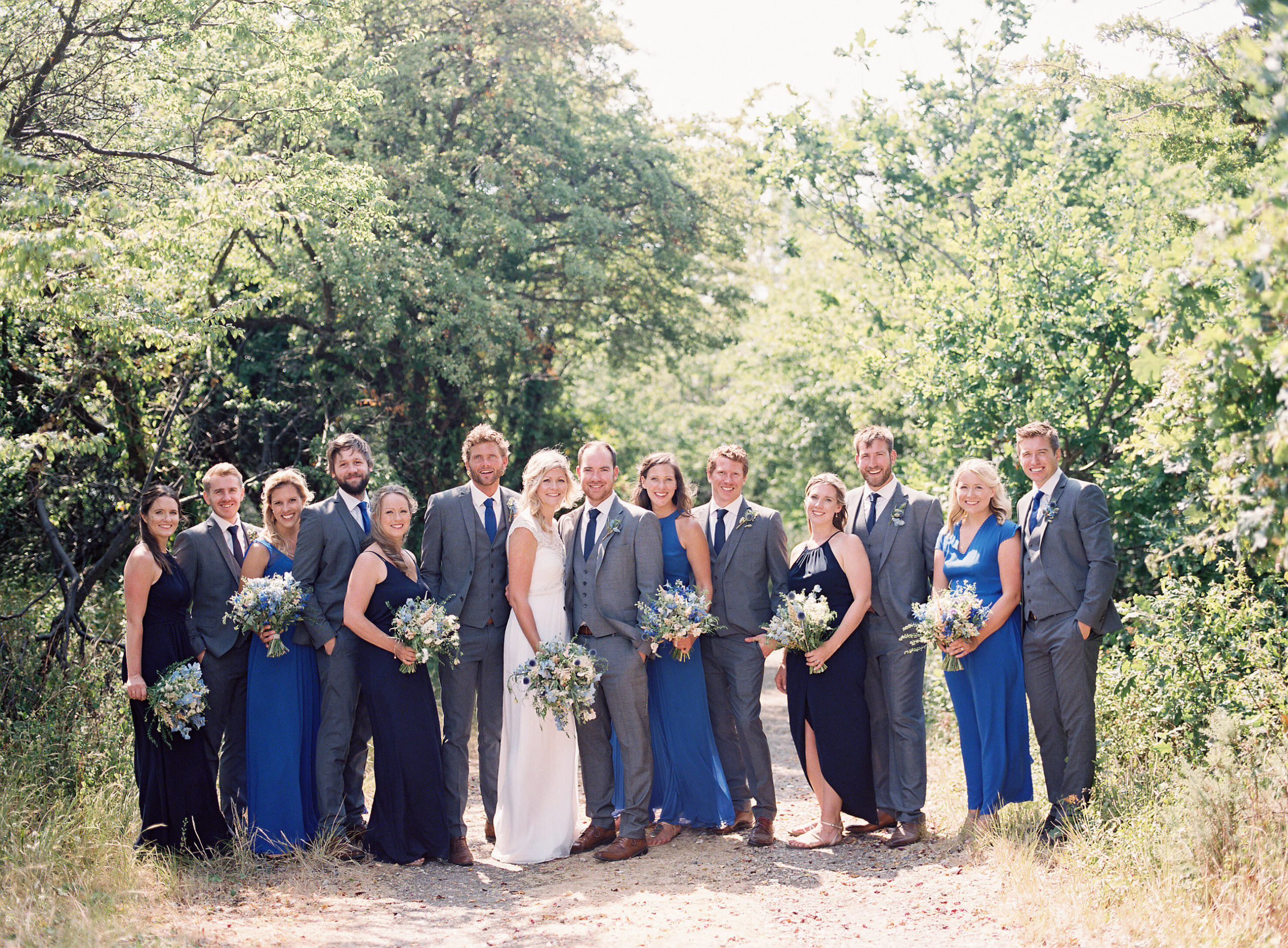 bridal party standing on a dusty path for group photo