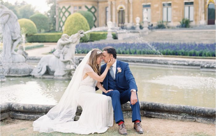 couple sitting beside fountain at Waddesdon Manor wedding