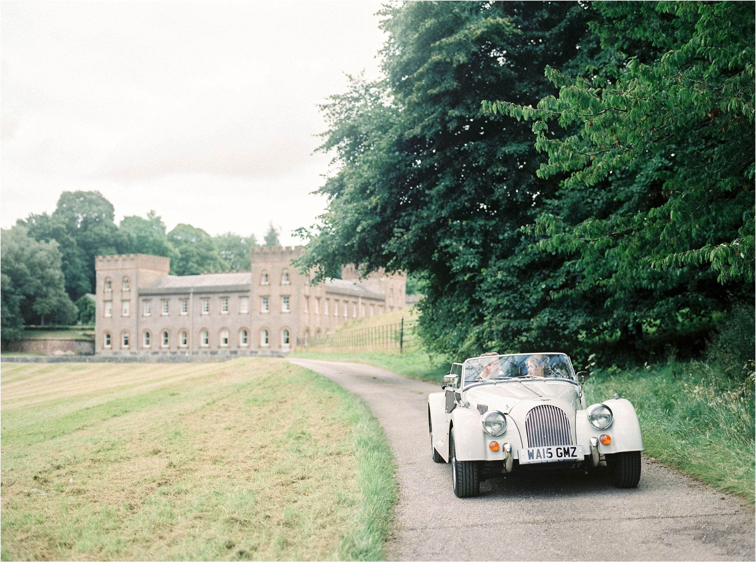 vintage car driving away from Ugbrooke House