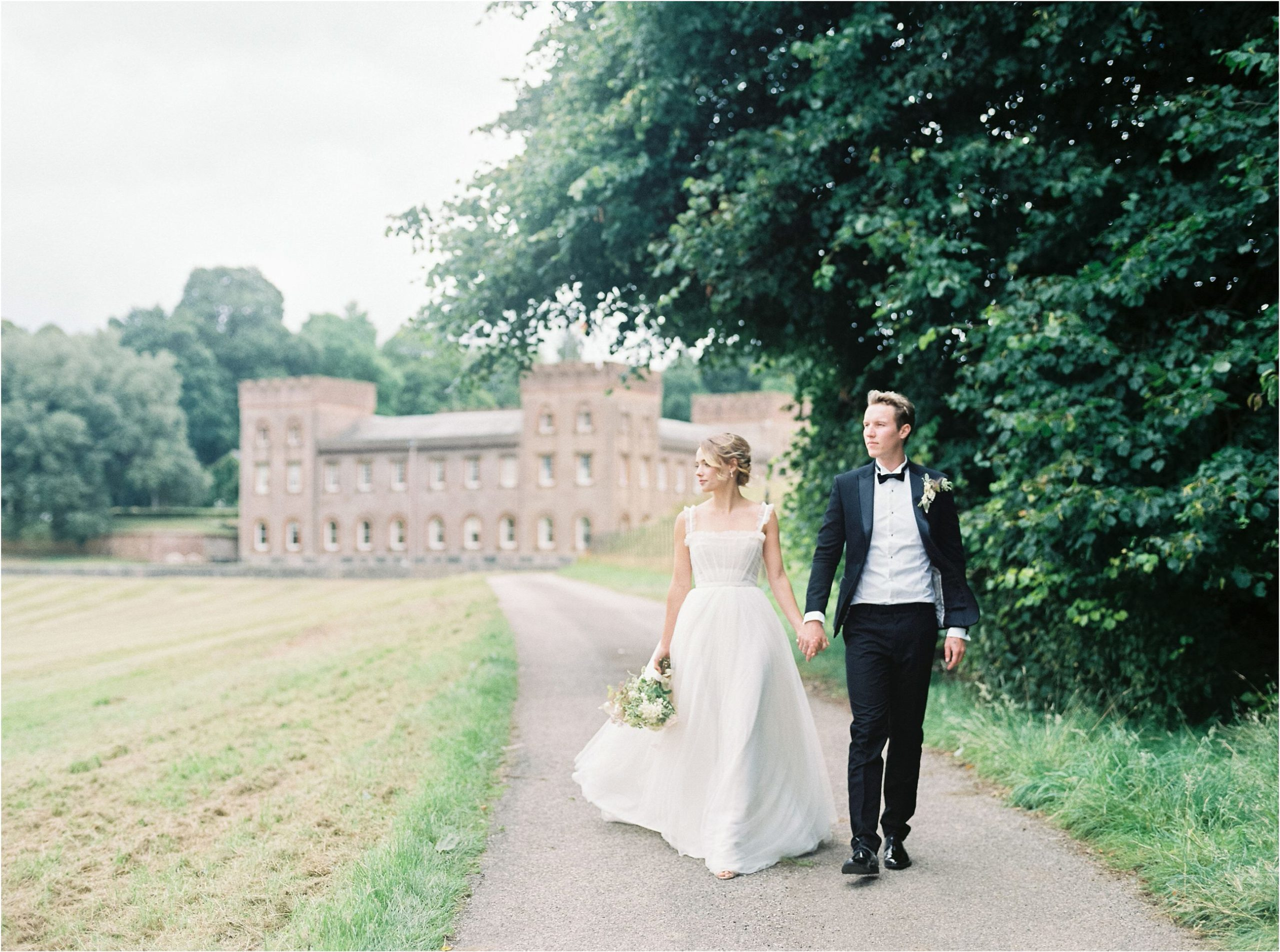 Bride and groom walking away from Ugbrooke House